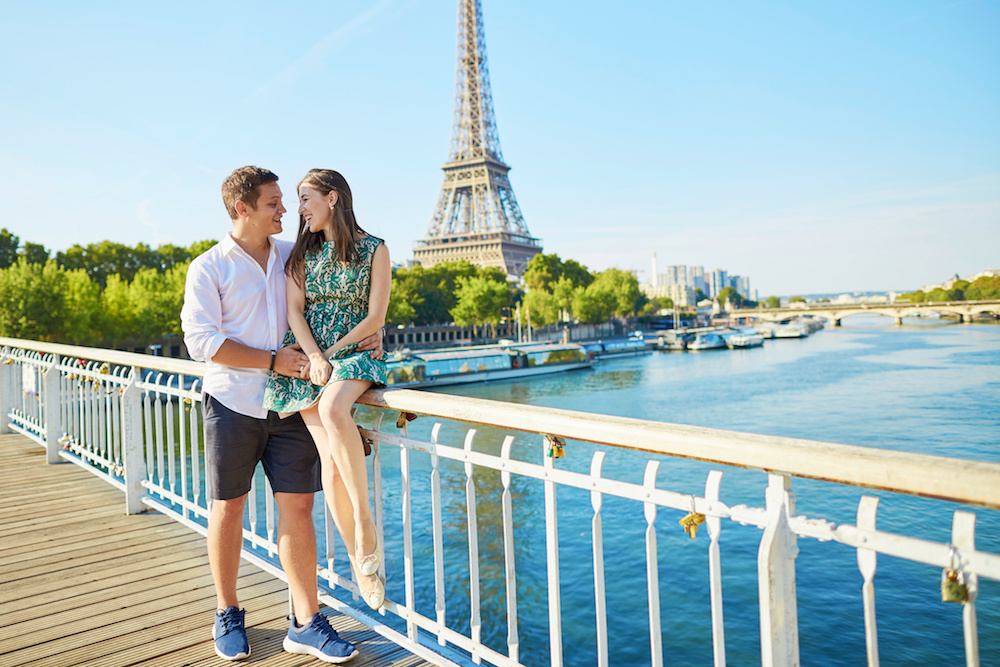 Young romantic couple spending their vacation in Paris, France. Dating couple posing near the Eiffel tower
