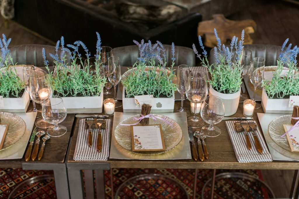 Wedding tabletop with textured chargers, wood elements, and greenery centerpiecees
