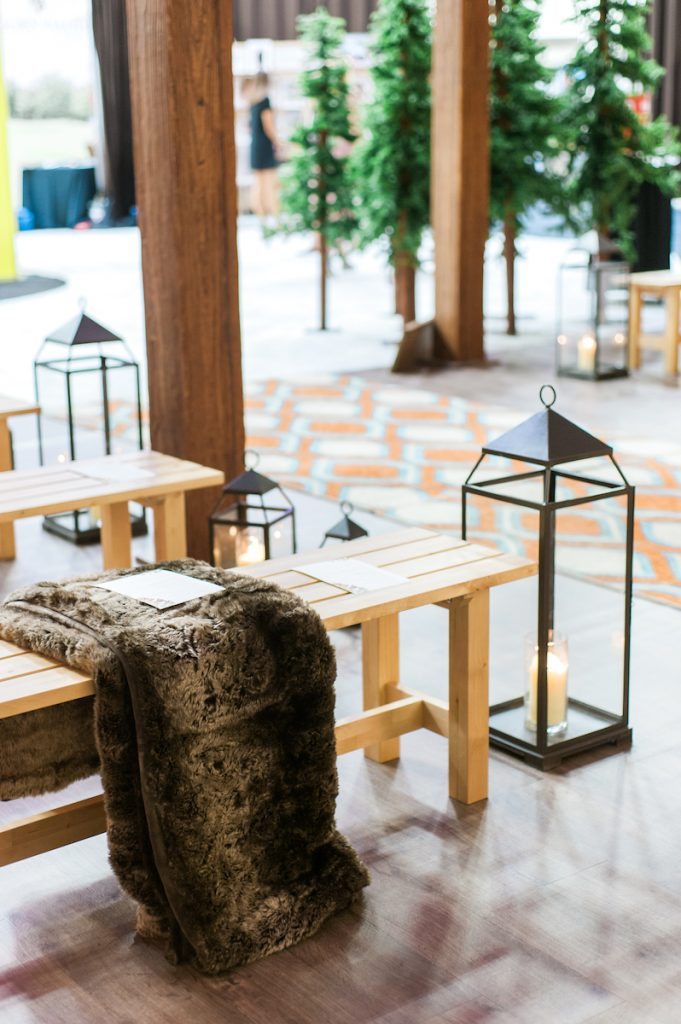 Rustic wedding ceremony seating with fur throws and lanterns
