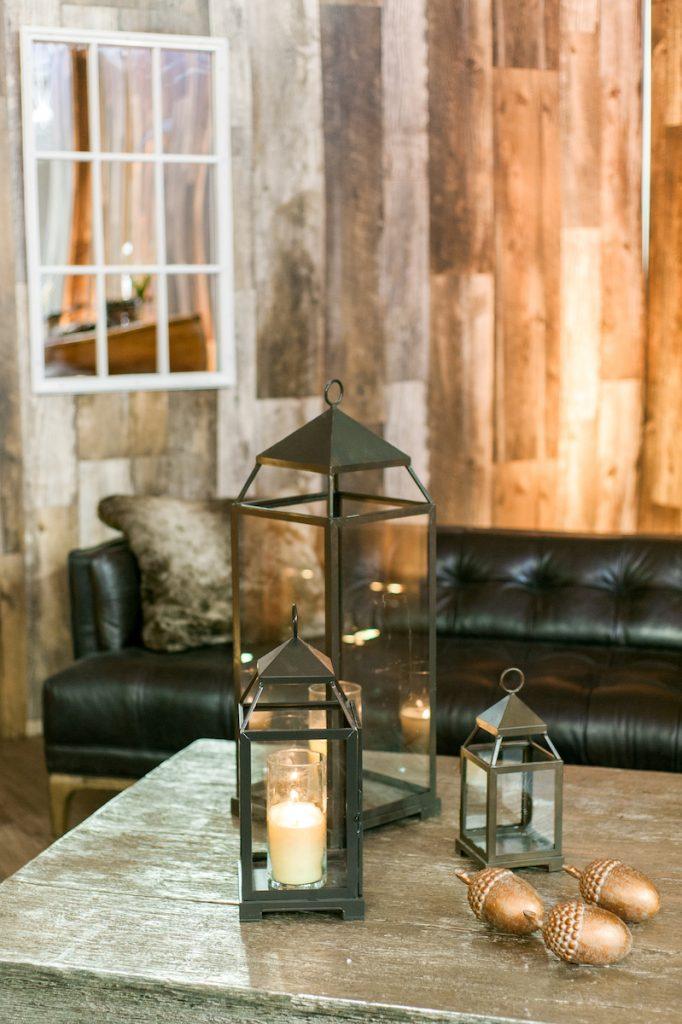 Black lanterns sit atop wedding lounge table