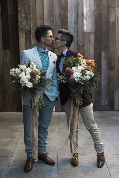 Two grooms coordinate same-sex wedding looks with complementary tuxedos