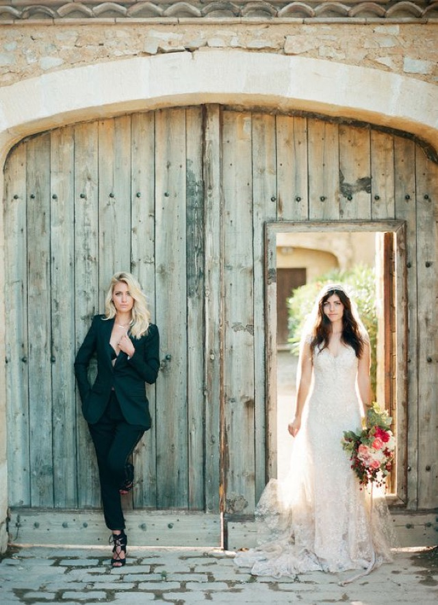 Bride wears black tux while the other bride wears a white bridal gown
