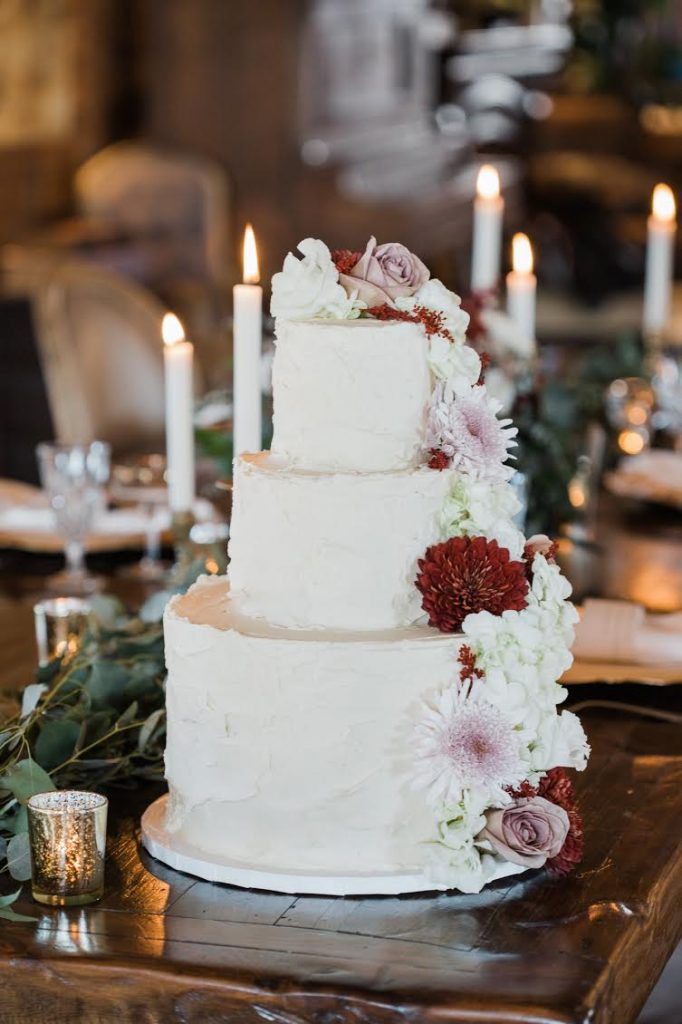 3-tier white wedding cake with real white, pink, and red flowers