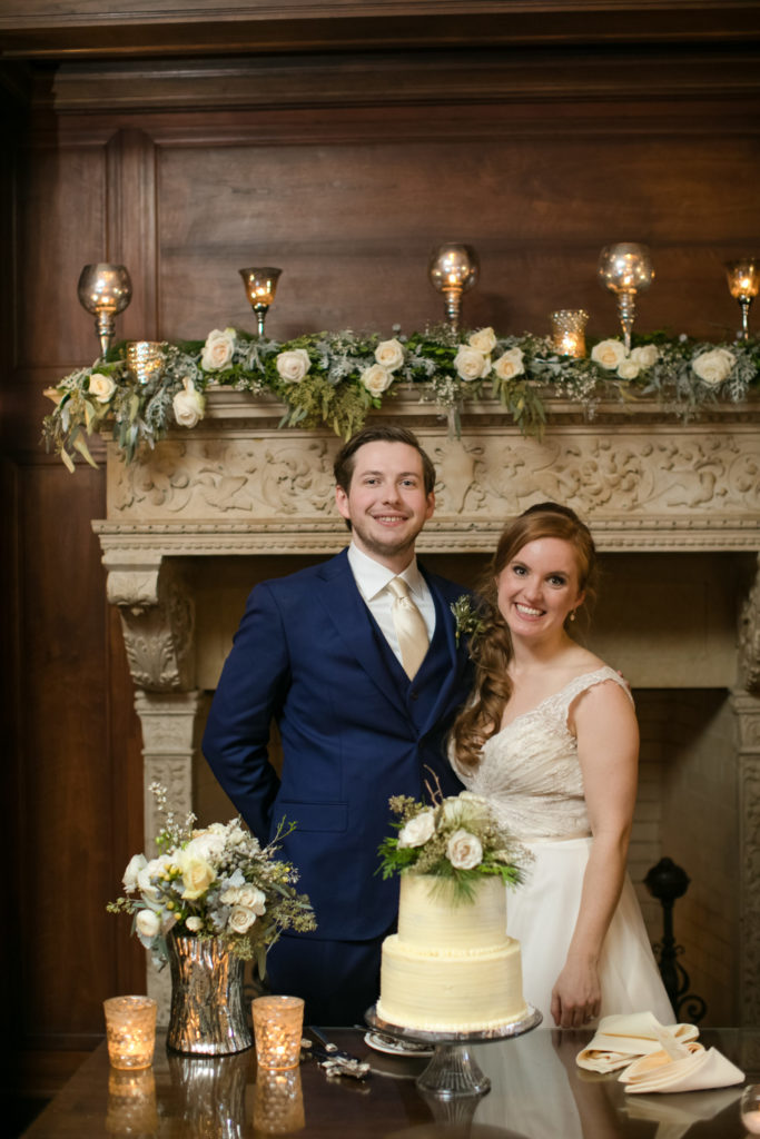Bride and groom pose in front of fire place at one of the best places to have your winter wedding