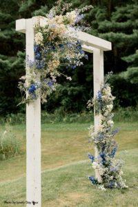Wedding ceremony arch wrapped with wild flowers