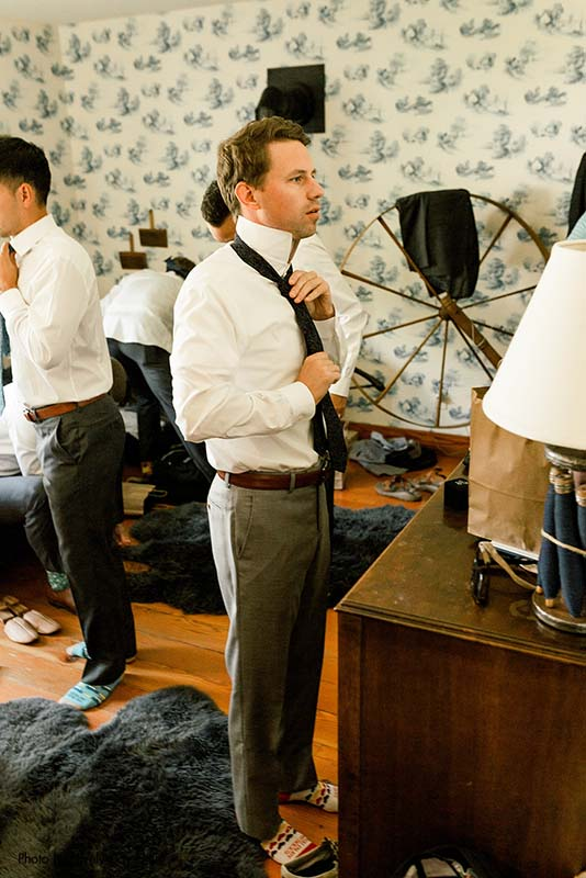 Groom puts on tie at Minnesota Real Wedding tips for grooms