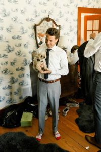 Groom poses with dog before wedding