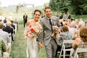 Bride and groom leave ceremony with dog