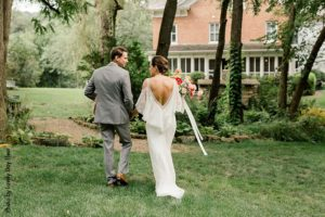 Bride in white boho dress and groom in gray suit after ceremony