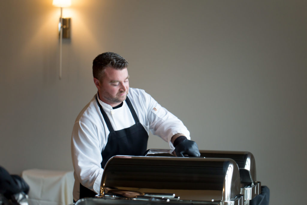 Chef Andrew Garner preps food in a warmer for wedding catering