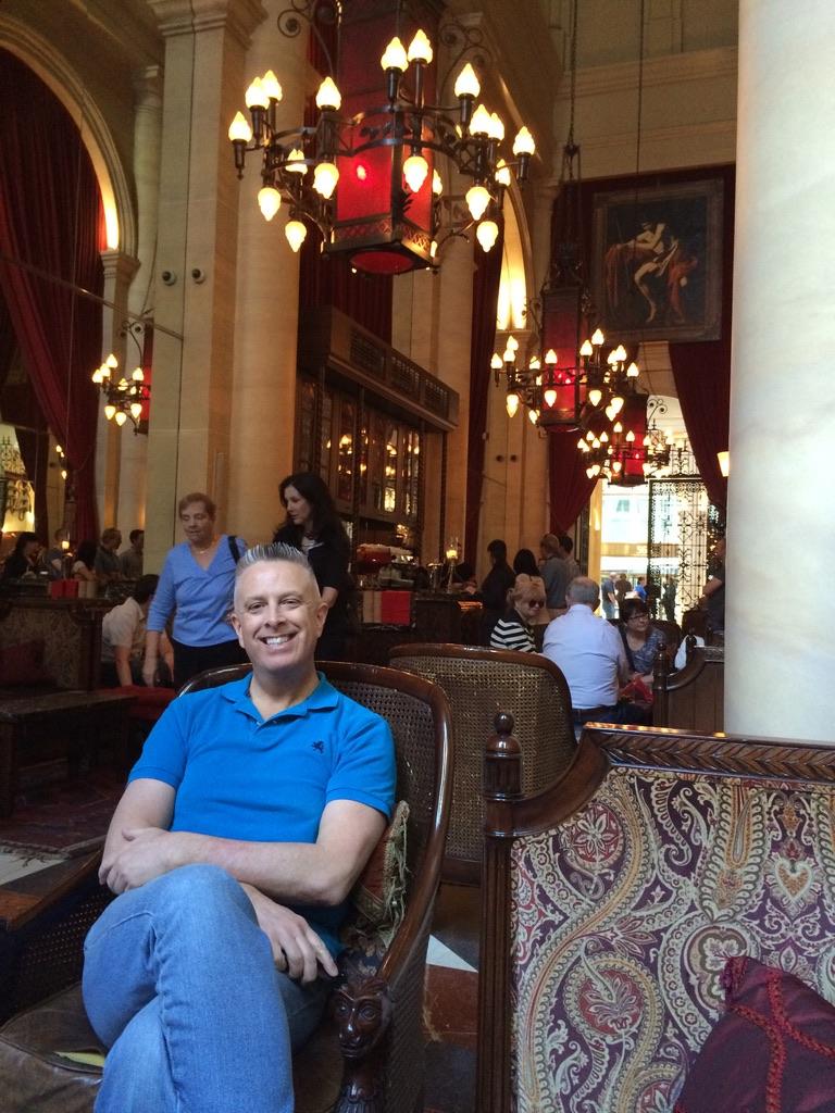 Man in blue shirt sits at restaurant