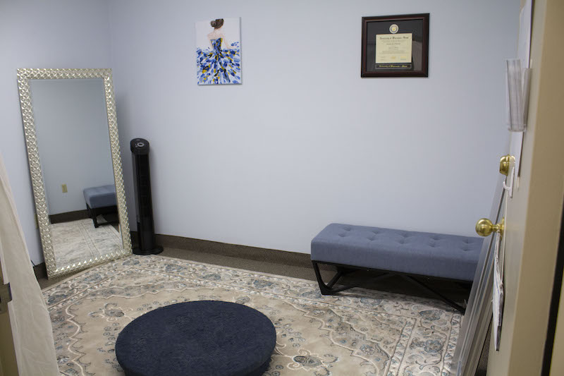 Alterations studio with bench, mirror, rug, and decor