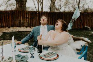 Bride and groom pop champagne bottle