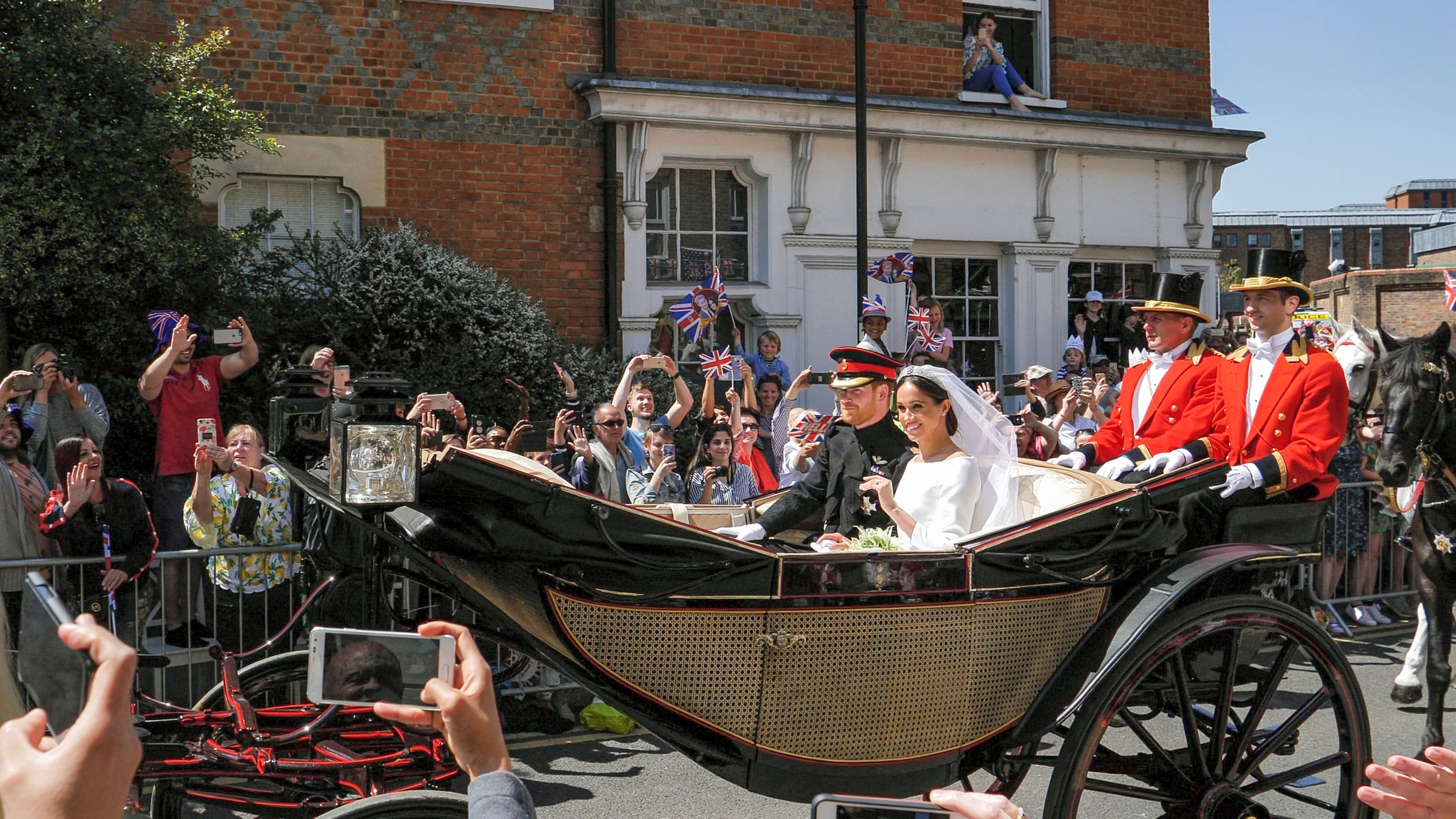 Prince Harry and Meghan Markle greet fans in carriage following royal weddings