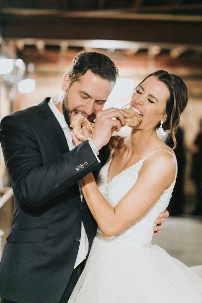 Bride and groom feed each other donuts at wedding