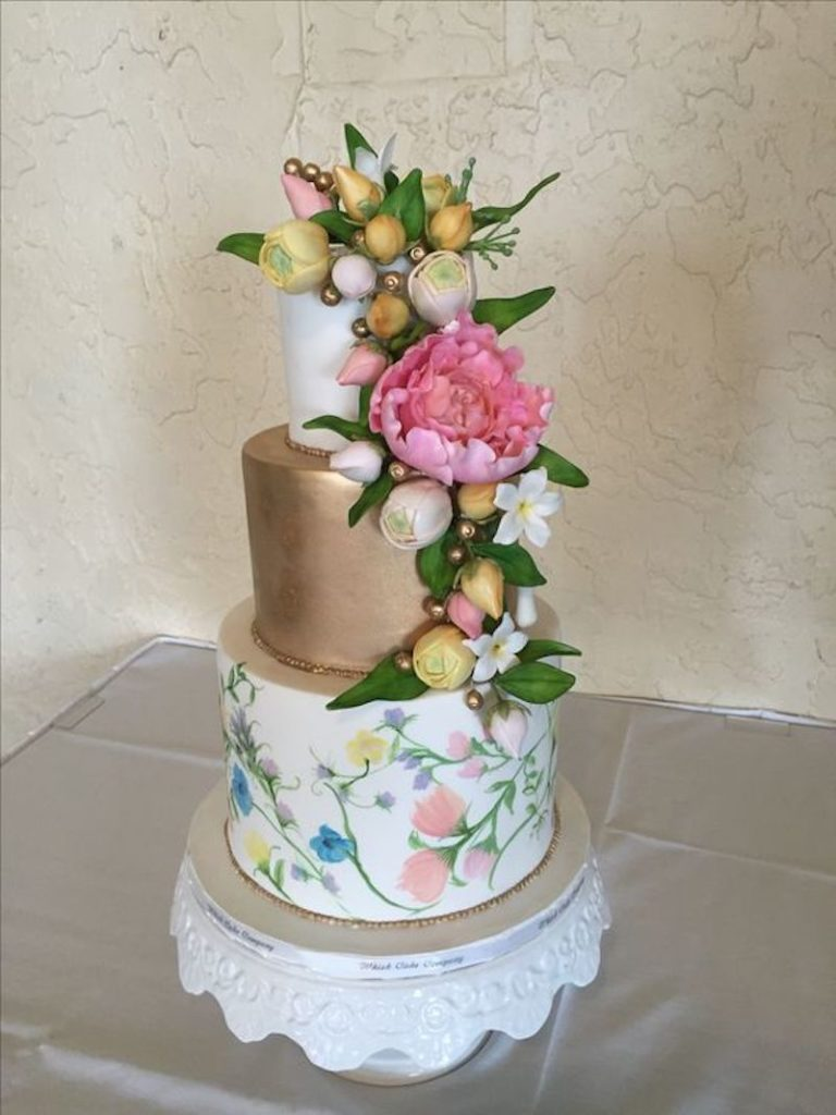 White and gold wedding cake with painted flowers