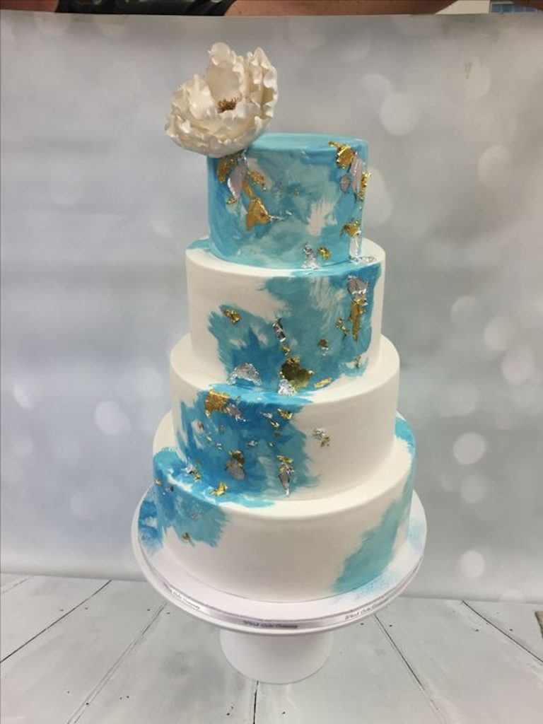 Blue and white wedding cake with gold flakes