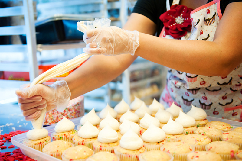 Baker frosts white wedding cupcakes at Nadia Cakes