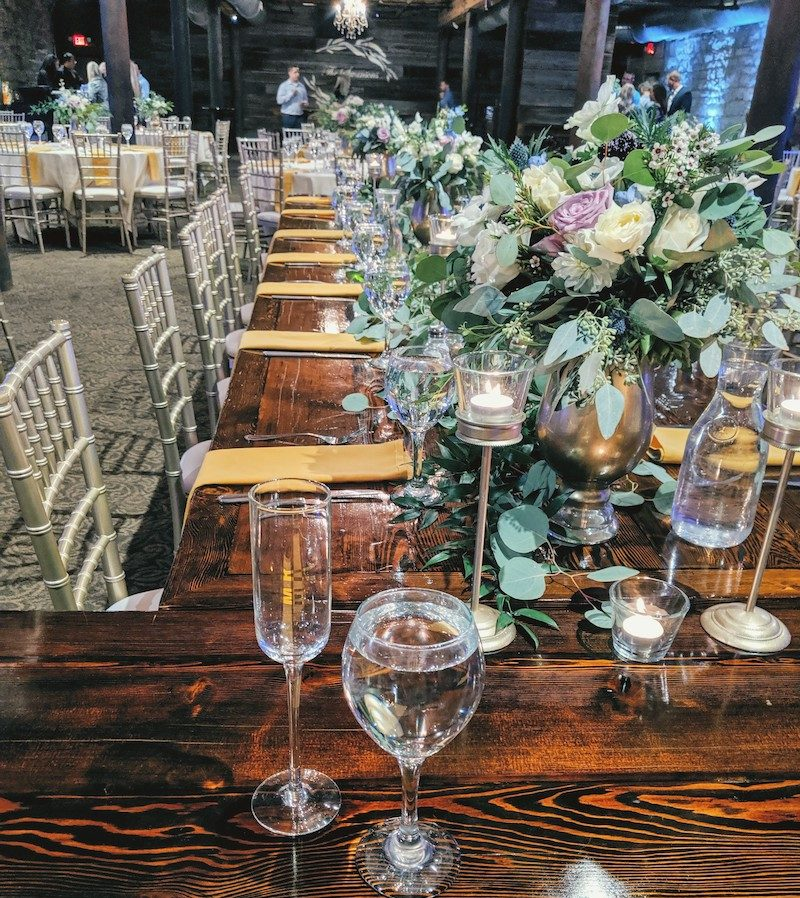 Eucalyptus bouquets and glassware on wooden wedding tabletop
