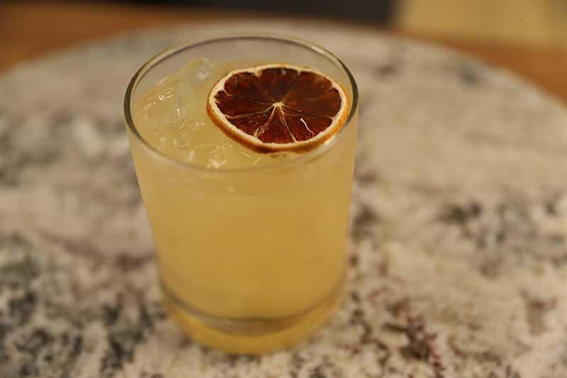 Honey whiskey sour cocktail garnished with burnt orange