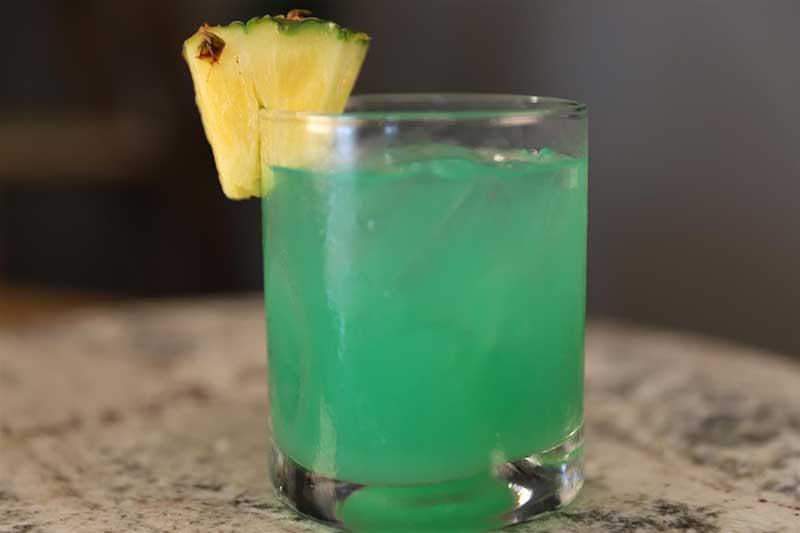 Blue rum cocktail garnished with pineapple