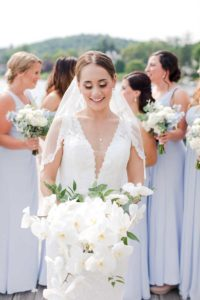 Bride in white dress with bridesmaids in blue dresses