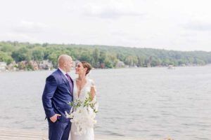 Bride in white dress groom in blue suit after lake wedding