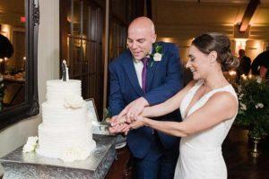 Groom in blue suit bride in white dress cut wedding cake