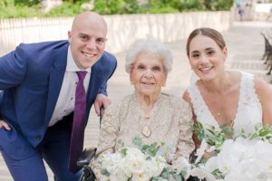 Bride in white dress groom in blue suit with grandmother