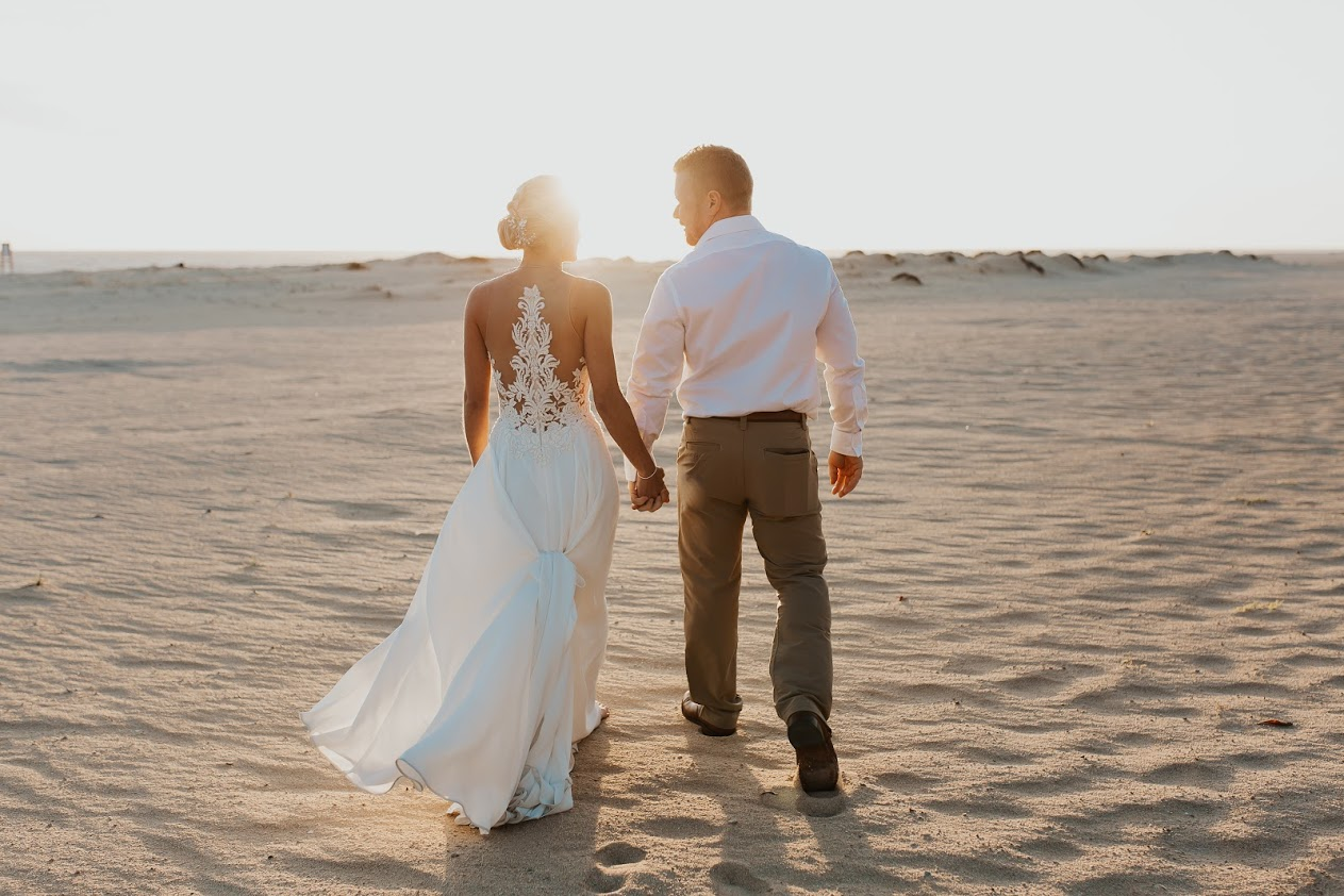 Bride in white dress groom in white shirt and tan pants walk on beach