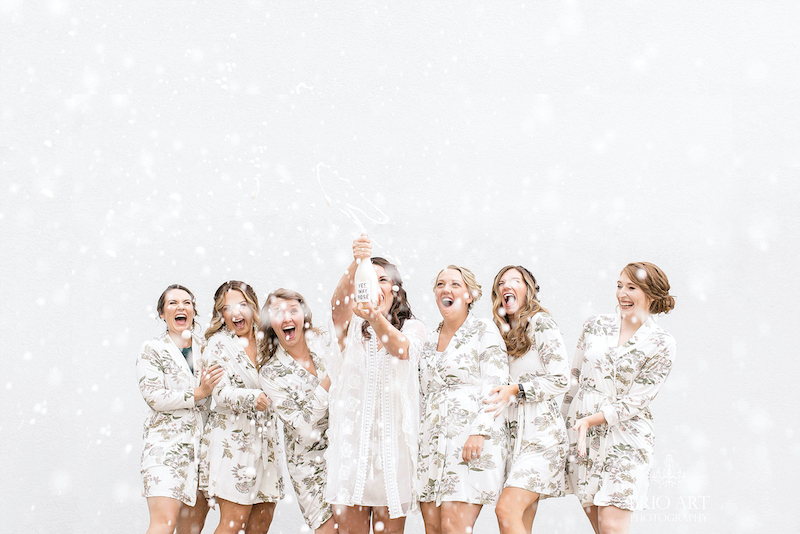 Bridal party pops champagne by Brio Art Photography