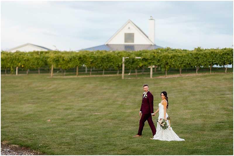 Bride and groom walk outside Bold North Cellars vineyard wedding venue