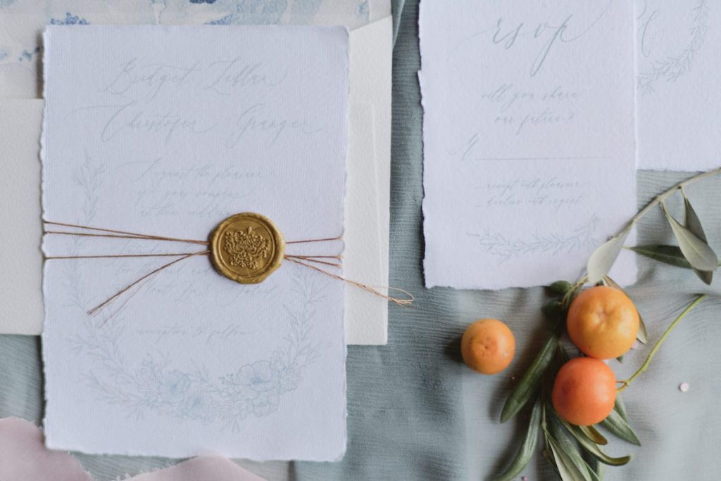 Pale blue and white wedding invites with gold was seal