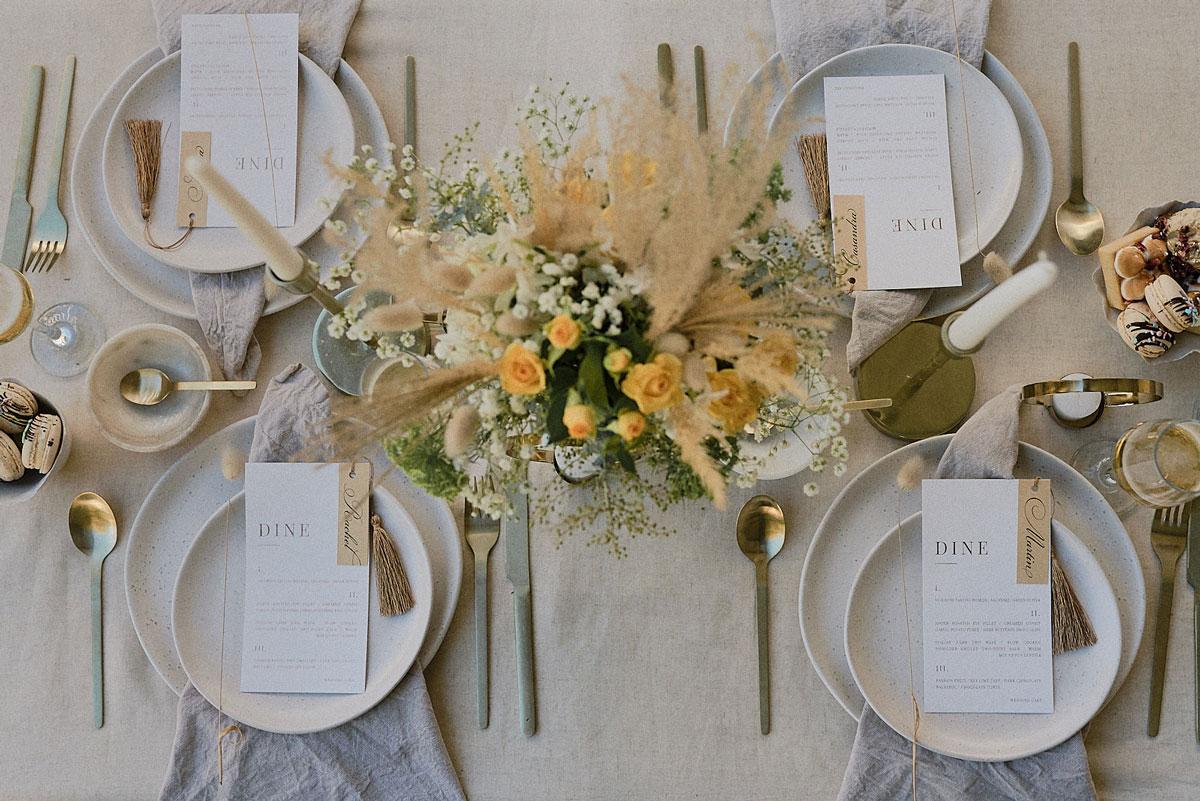 Neutral palette wedding table with unbleached linen and spotted pottery