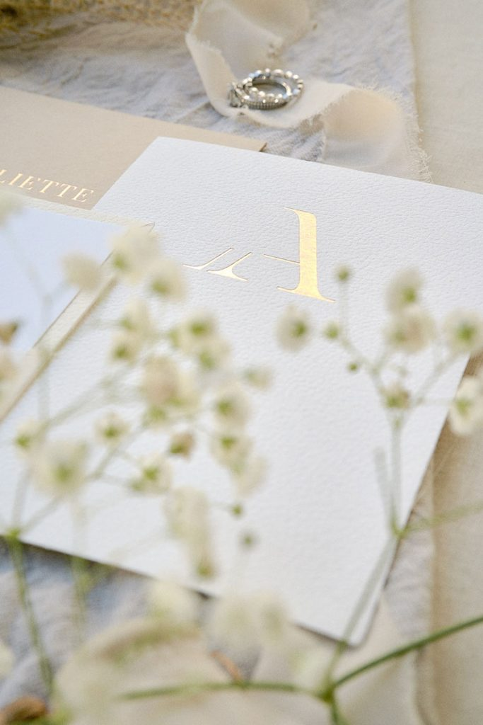 """White wedding invitation with gold embossed """"A"""""""