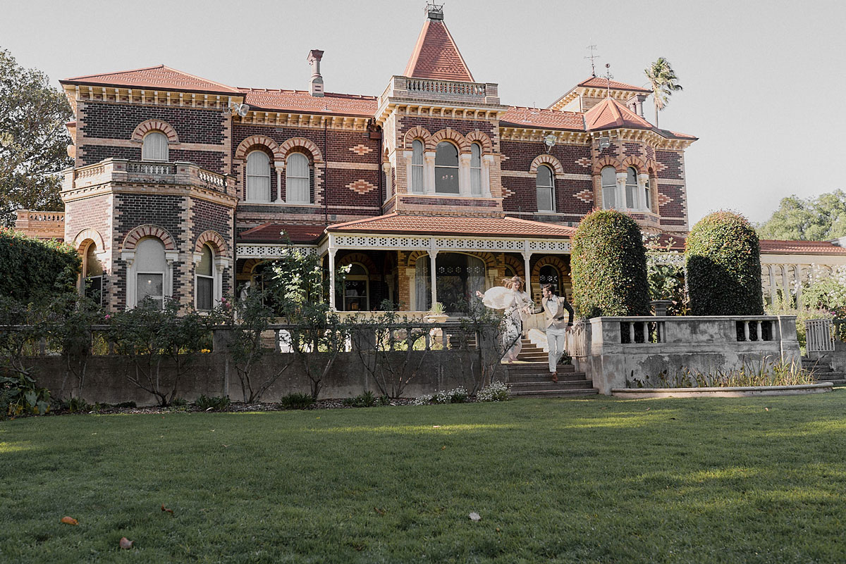 Bride and groom walk out of large Victorian dreams home after wedding