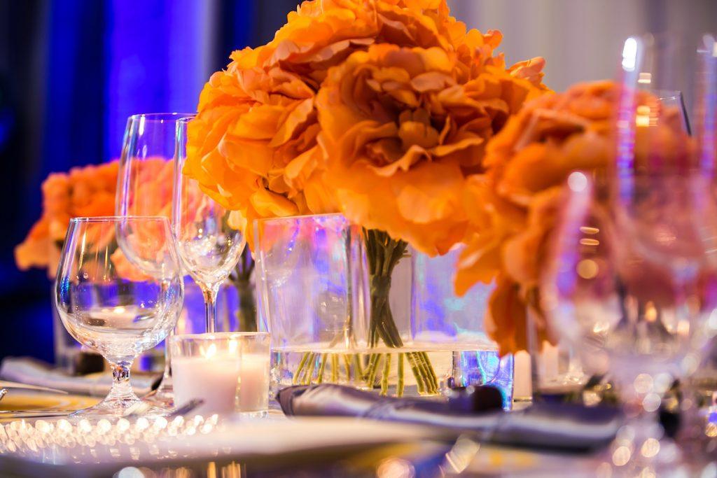 Orange flowers in silver vases at wedding