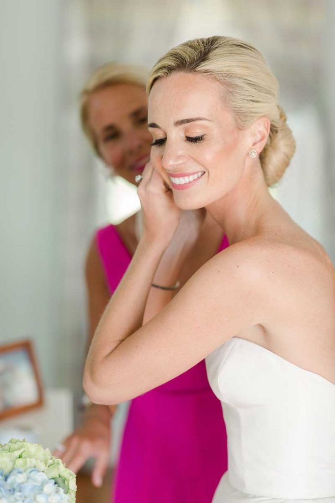 Bride puts on earrings before ceremony