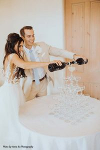 Bride and groom pour champagne into glass tower