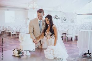 Bride and groom cut cake by D'amico Catering