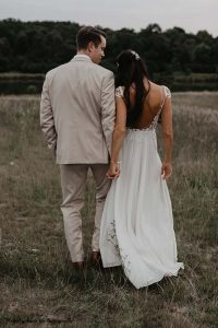 Bride and groom pose for moody outdoor photo