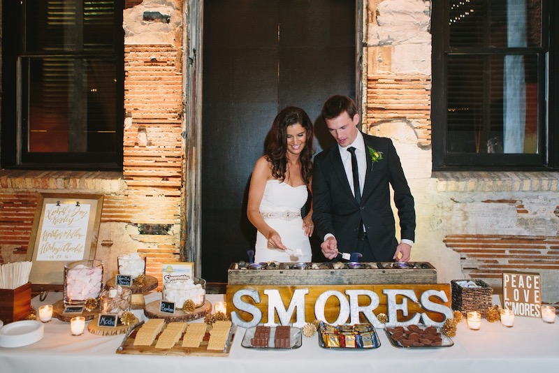 Bride and groom roast marshmallows over fire at s'mores bar by North mallow