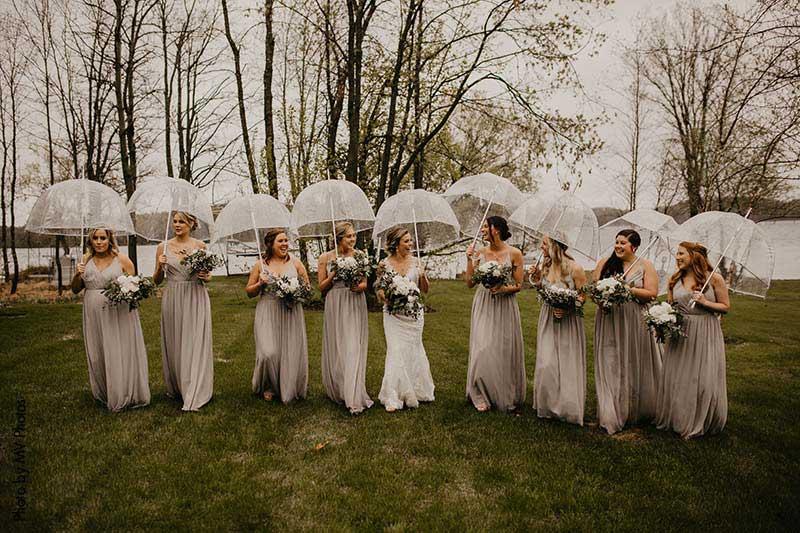 Bride and bridesmaids handle unpredictable weather with umbrellas