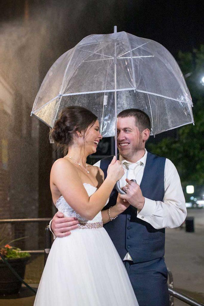 Bride and groom stand under umbrella