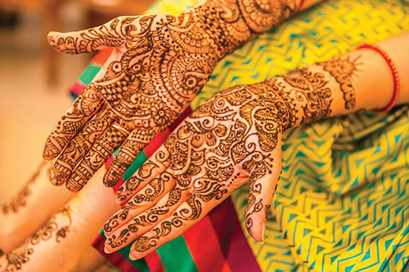 Bride gets henna art on hands before cultural wedding