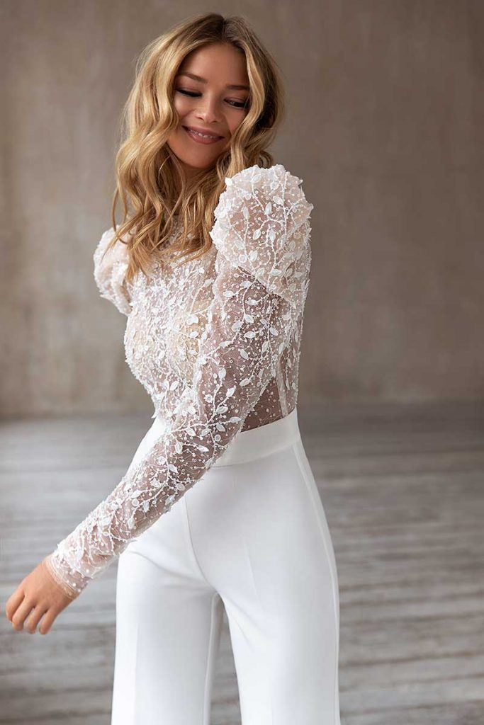 Bride in embroidered top with white pants by Eva Lendel
