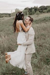 Bride holds up groom after elegant Minnesota wedding