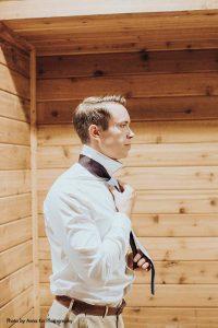 Grooms puts on tie before elegant Minnesota wedding