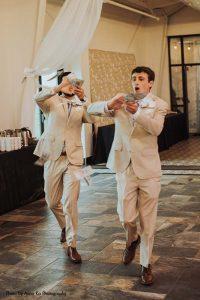 Groomsmen in tan suits throw cash walking into reception