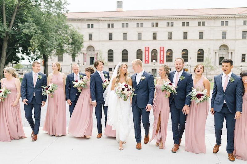 Wedding party walks outside The Saint Paul Hotel Minnesota luxury wedding venue